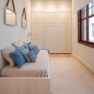 Modelo de habitación de invitados actual, de tamaño medio, sin chimenea, con paredes blancas, suelo de madera en tonos medios y suelo marrón