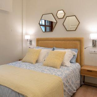 Diseño de dormitorio contemporáneo, de tamaño medio, sin chimenea, con paredes blancas, suelo laminado y suelo marrón