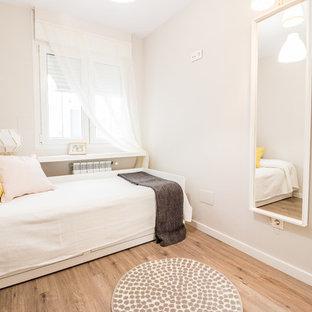 Ejemplo de habitación de invitados actual, pequeña, con suelo laminado, paredes beige y suelo beige