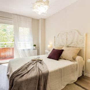 Foto de habitación de invitados actual, pequeña, con suelo laminado, paredes beige y suelo beige