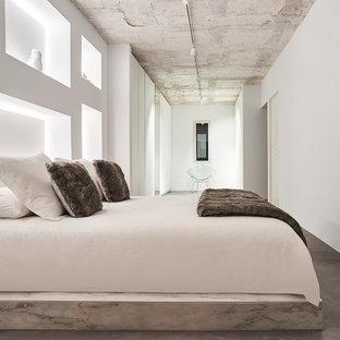 Modelo de dormitorio principal, minimalista, grande, sin chimenea, con paredes blancas y suelo de cemento
