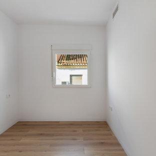 Bild på ett mellanstort funkis huvudsovrum, med vita väggar och laminatgolv