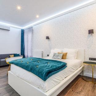 Foto de dormitorio principal, actual, con paredes blancas, suelo de madera en tonos medios y suelo marrón