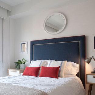 Diseño de habitación de invitados costera, grande, con suelo de madera en tonos medios, suelo marrón y paredes blancas