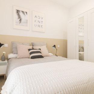 Modelo de dormitorio contemporáneo, sin chimenea, con paredes blancas y suelo de madera clara