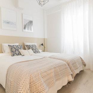 Diseño de dormitorio contemporáneo, sin chimenea, con paredes beige y suelo de madera clara