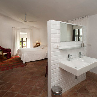 This is an example of a large country master bedroom in Seville with white walls and terra-cotta floors.