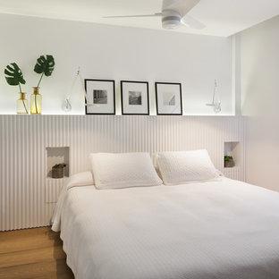 Idée de décoration pour une chambre d'amis marine avec un mur blanc, un sol en bois brun et un sol beige.