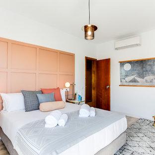Imagen de dormitorio principal, contemporáneo, con paredes blancas, suelo de madera clara y suelo marrón