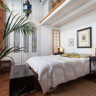 Diseño de dormitorio tipo loft, tropical, de tamaño medio, sin chimenea, con paredes blancas y suelo de baldosas de terracota