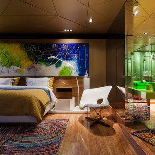 Modelo de dormitorio principal, actual, grande, con suelo de madera en tonos medios, suelo marrón y paredes marrones