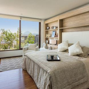 Modelo de dormitorio principal, contemporáneo, grande, con suelo de madera oscura, paredes beige y suelo marrón