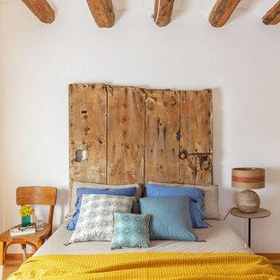 Foto de dormitorio mediterráneo, grande, con paredes blancas, suelo de madera en tonos medios y suelo marrón