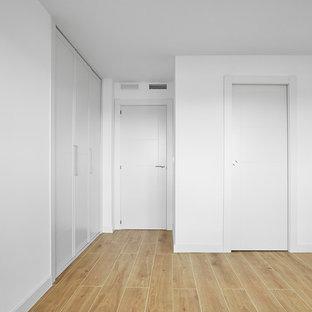 Ejemplo de dormitorio principal, escandinavo, de tamaño medio, con paredes blancas, suelo de baldosas de terracota y suelo marrón