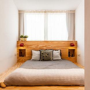Imagen de dormitorio actual con paredes blancas, suelo de contrachapado y suelo marrón