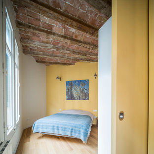 Foto de dormitorio principal, industrial, de tamaño medio, sin chimenea, con paredes amarillas y suelo de madera en tonos medios