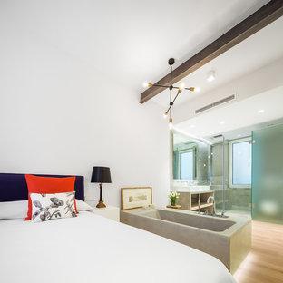 Modelo de dormitorio principal, actual, de tamaño medio, sin chimenea, con paredes blancas y suelo de madera clara