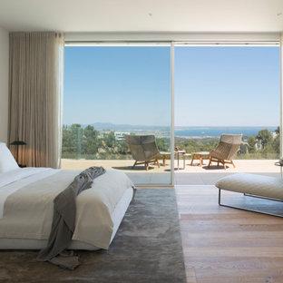 Imagen de dormitorio moderno con paredes blancas, suelo de madera en tonos medios y suelo marrón