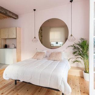 Ejemplo de dormitorio tropical, extra grande, con paredes rosas, suelo de madera clara y suelo marrón