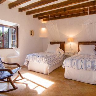 Imagen de habitación de invitados mediterránea, grande, sin chimenea, con paredes blancas y suelo de baldosas de terracota