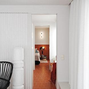 Diseño de dormitorio principal, minimalista, de tamaño medio, sin chimenea, con paredes blancas, suelo de baldosas de terracota y suelo marrón