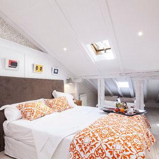 Ejemplo de dormitorio principal, ecléctico, pequeño, con paredes blancas, suelo de madera clara, chimenea tradicional y marco de chimenea de ladrillo