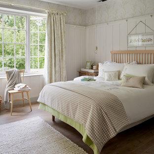 Modelo de dormitorio principal, de estilo de casa de campo, de tamaño medio, sin chimenea, con paredes blancas y suelo de madera en tonos medios