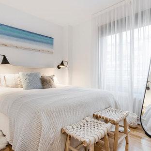 Foto de dormitorio principal, marinero, pequeño, sin chimenea, con paredes blancas, suelo de madera en tonos medios y suelo marrón