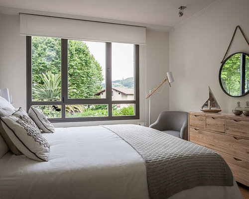 Small minimalist master light wood floor bedroom photo in bilbao with white walls