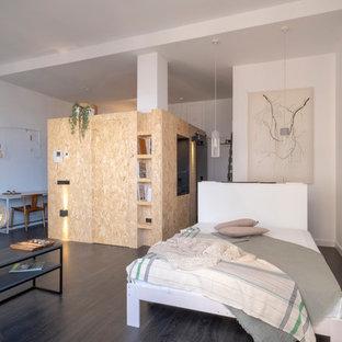 Foto de dormitorio urbano con paredes blancas, suelo de madera oscura y suelo marrón