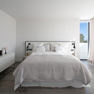 Modelo de dormitorio principal, contemporáneo, con paredes blancas, suelo de madera en tonos medios y suelo marrón