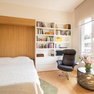 Modelo de habitación de invitados actual, de tamaño medio, con paredes blancas y suelo de madera clara