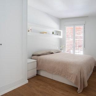 Ejemplo de dormitorio contemporáneo con paredes blancas, suelo de madera en tonos medios y suelo marrón