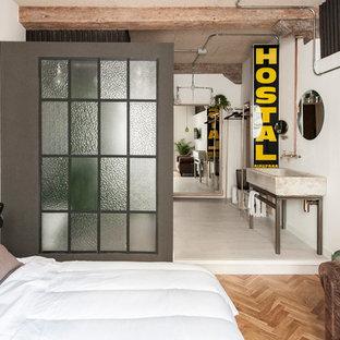 Ejemplo de dormitorio tipo loft, industrial, de tamaño medio, sin chimenea, con paredes blancas y suelo de madera en tonos medios