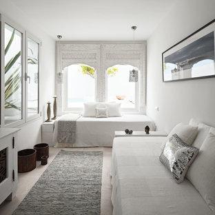 Inspiration för mellanstora medelhavsstil gästrum, med vita väggar och travertin golv