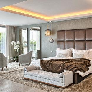 Foto de dormitorio principal, actual, grande, con paredes grises, suelo de madera clara y suelo beige