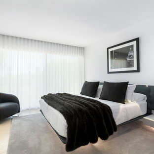This is an example of a contemporary bedroom in Other with white walls and beige floors.