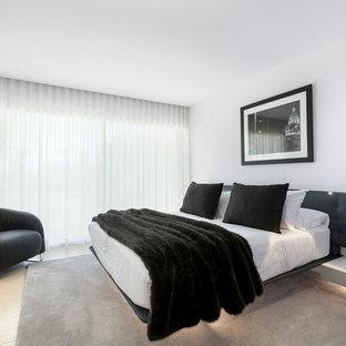 Foto de dormitorio contemporáneo con paredes blancas y suelo beige
