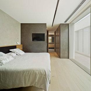 Modelo de dormitorio minimalista, grande, con paredes grises, suelo de madera clara y suelo beige