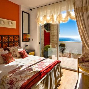 Inspiration för ett mellanstort medelhavsstil huvudsovrum, med orange väggar och mellanmörkt trägolv