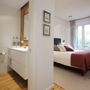 Imagen de dormitorio principal, actual, de tamaño medio, con paredes blancas, suelo de madera clara y suelo beige