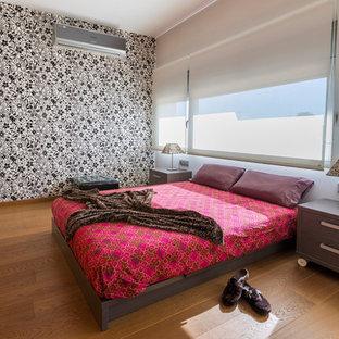 Ejemplo de habitación de invitados contemporánea, grande, sin chimenea, con paredes multicolor, suelo de madera en tonos medios y suelo marrón