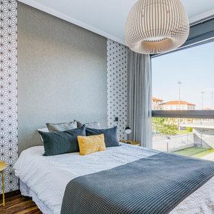 Imagen de dormitorio principal, actual, de tamaño medio, sin chimenea, con paredes grises, suelo de madera en tonos medios y suelo marrón