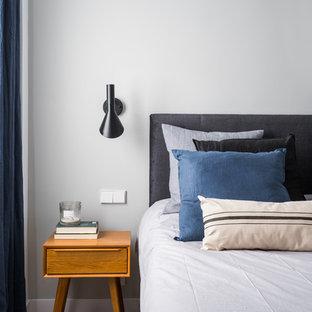 Imagen de dormitorio actual con paredes grises, suelo de madera clara y suelo beige