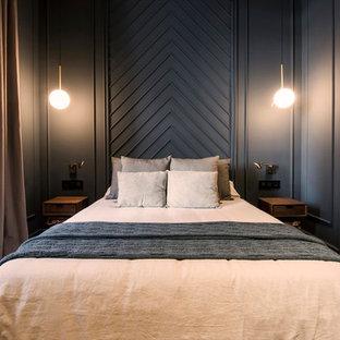 Ejemplo de dormitorio principal, tradicional renovado, de tamaño medio, con paredes negras, suelo de madera en tonos medios y suelo marrón