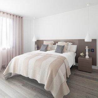 Ejemplo de dormitorio principal, contemporáneo, de tamaño medio, sin chimenea, con paredes blancas y suelo de madera en tonos medios