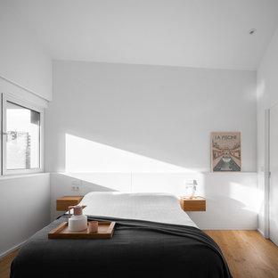 Diseño de dormitorio moderno con paredes blancas, suelo de madera en tonos medios y suelo marrón