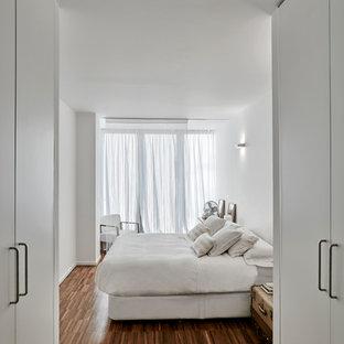 Ejemplo de dormitorio principal, actual, grande, sin chimenea, con paredes blancas, suelo de madera en tonos medios y suelo marrón
