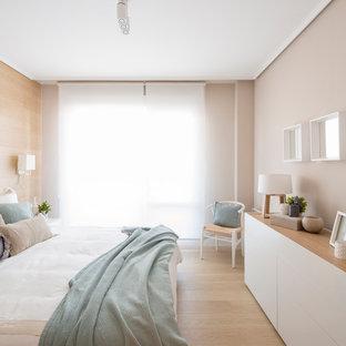 Ejemplo de dormitorio principal, nórdico, de tamaño medio, sin chimenea, con paredes beige y suelo de madera clara