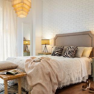 Ejemplo de dormitorio ladrillo, actual, ladrillo, con paredes blancas, suelo de madera en tonos medios, suelo marrón y ladrillo
